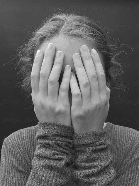 Portrait of teenage girl with hands covering face, close